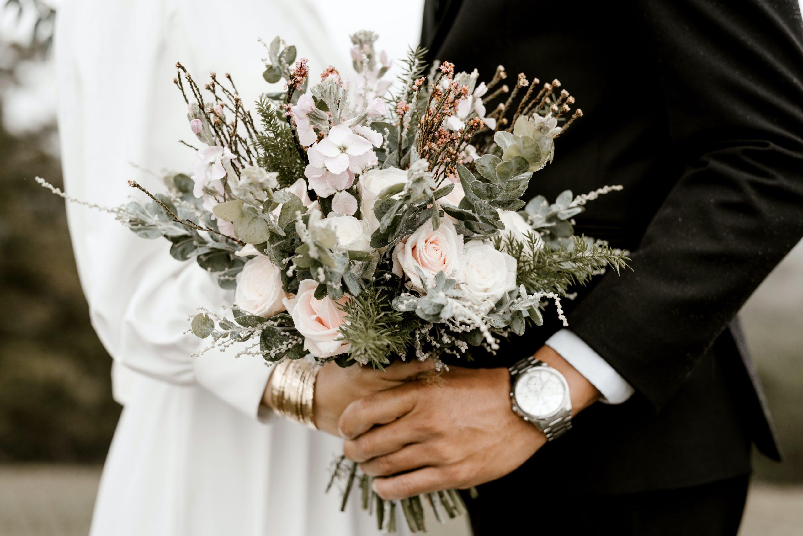 Couple holding wedding flowers.