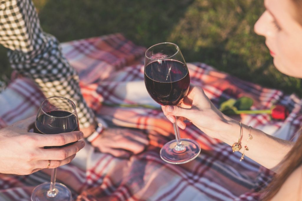 A couple, sat drinking red wine on a picnic blanket.